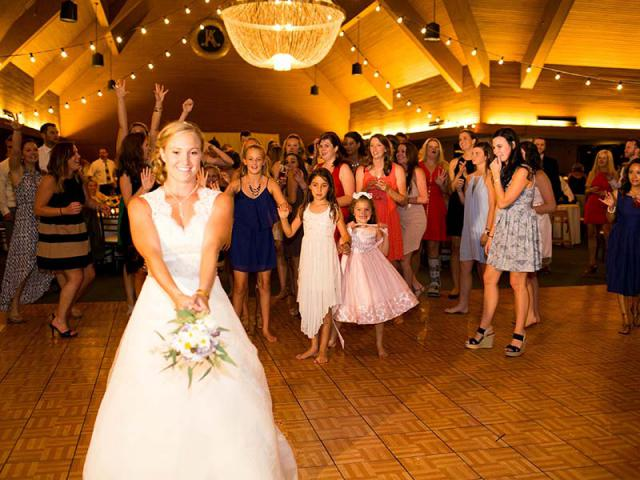 Bride tossing bouquet at summer wedding